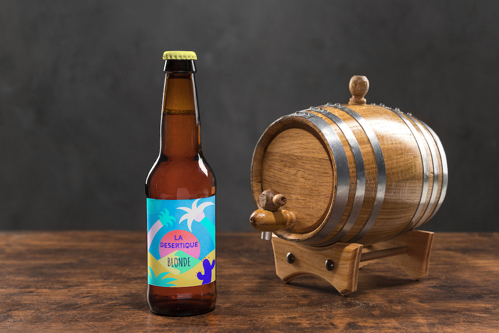 blond beer bottle on a table with a cask and an illustrated label showing a desert and palms